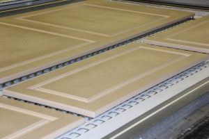Photo of doors with glue applied awaiting thermo-laminating.